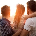 Young gay parents with their daughter having fun in park. Parents holding girl in arms. Enjoying in beautiful sunset. Caucasian ethnicity.